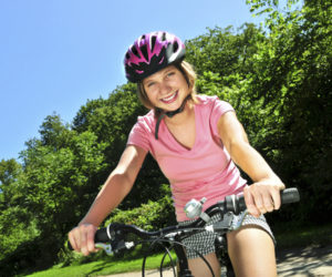 Portrait of a teenage girl on a bicycle in summer park outdoors